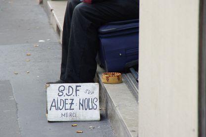 """Une pancarte aux pieds d'un sans-abri, sur laquelle est marqué : """"SDF, aidez-nous, merci"""""""