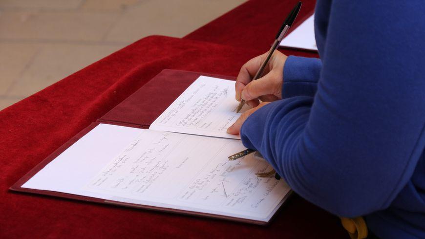Une personne écrit un message dans un registre de condoléances (image d'illustration)