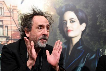 """Tim Burton, réalisateur, scénariste et producteur de cinéma américain, devant une affiche de son film """"Miss Peregrine"""" avec Eva Green (2016)"""