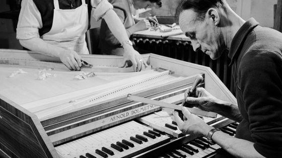 Des luthiers travaillant sur un clavecin