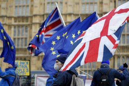 Un militant porte un drapeau de l'Union et un drapeau de la croix de Saint-Georges alors qu'il passe devant des militants anti-Brexit brandissant des drapeaux de l'Union européenne.