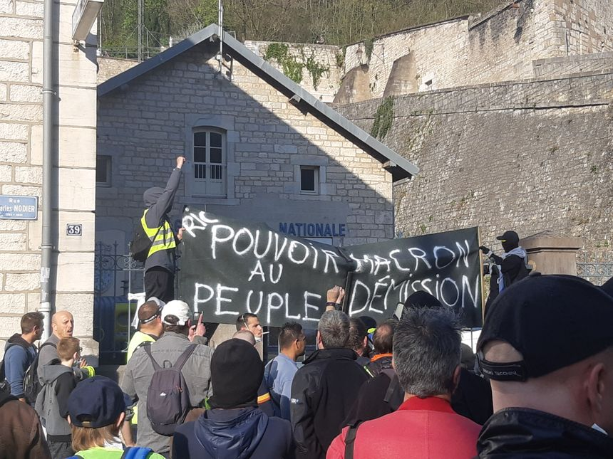 Des manifestants masqués déploient une banderole sur les grilles de la gendarmerie de Tarragnoz