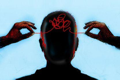 Les mains démêlent le fil de l'intérieur de la tête de l'homme.