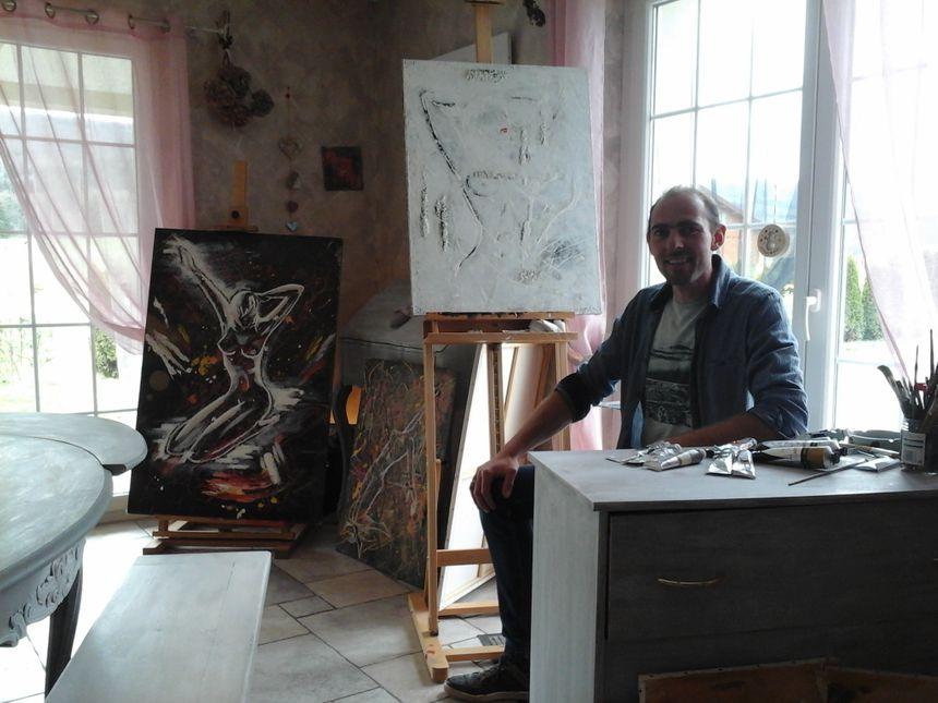 Aoguste devant 3 de ses toiles, la vie au village en toile de fond