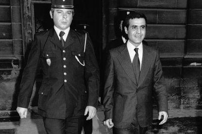 Pierre Goldman à côté d'un gendarme à son procès le 4 mai 1976 à Amiens