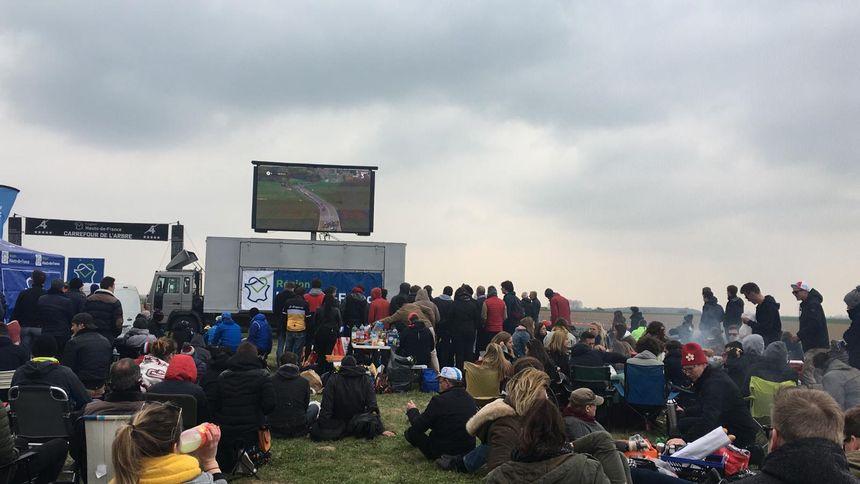 Le public suit la retransmission de la course avant de les voir au carrefour de l'arbre