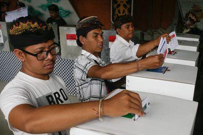 Des électeurs indonésiens à Bali en train de mettre leur bulletin dans l'urne