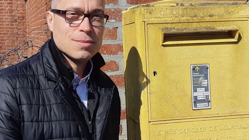 Aymeric Robin, le maire PC de Raismes devant la dernière boîte jaune de la Poste dans le quartier