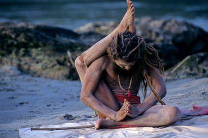 Sadhu pratiquant le yoga près des rives du Gange