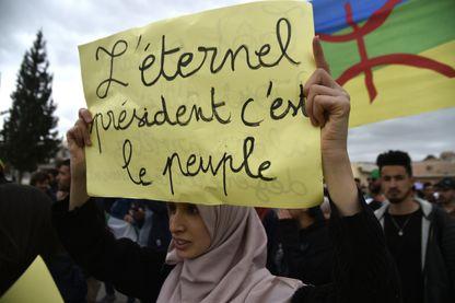 """Une femme algérienne manifestate contre le président Abdelaziz Bouteflika ; sur sa pancarte on peut lire """"L'éternel président c'est le peuple"""""""