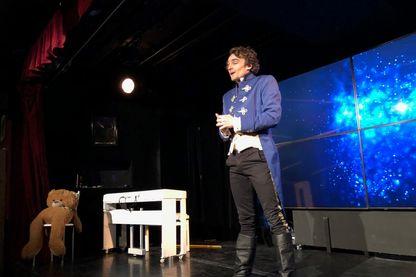 Derrière le chanteur comédien Adri1 et son ours Michel sur la scène du théâtre, l'écran géant sert à faire le lien avec le public