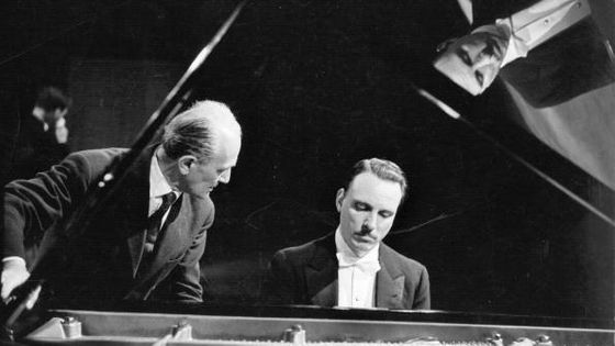 26th June 1959: Italian pianist Arturo Benedetti Michelangeli (1920 - 1995), (right), and his tuner Ettore Tallone at the piano during a concert tour