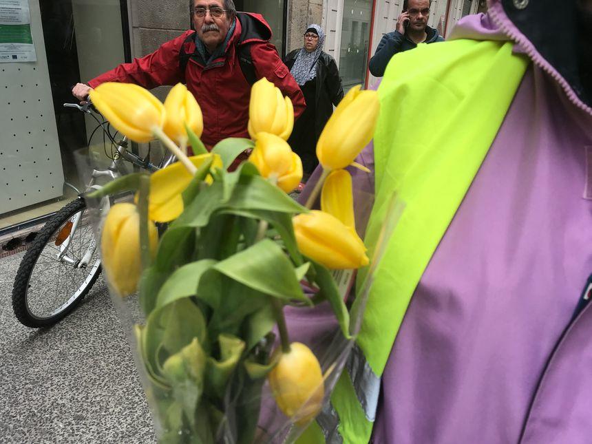 """Les """"gilets jaunes"""" stéphanois distribuent des tulipes aux passants."""