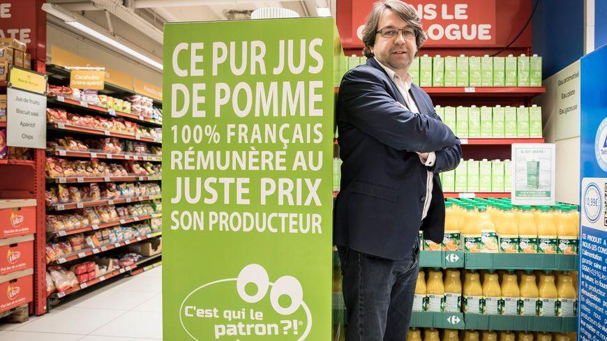 """Nicolas Chabanne, créateur de la marque du consommateur """" C'est qui le patron ?! """" pose devant le jus de pomme qui fête ses deux ans."""