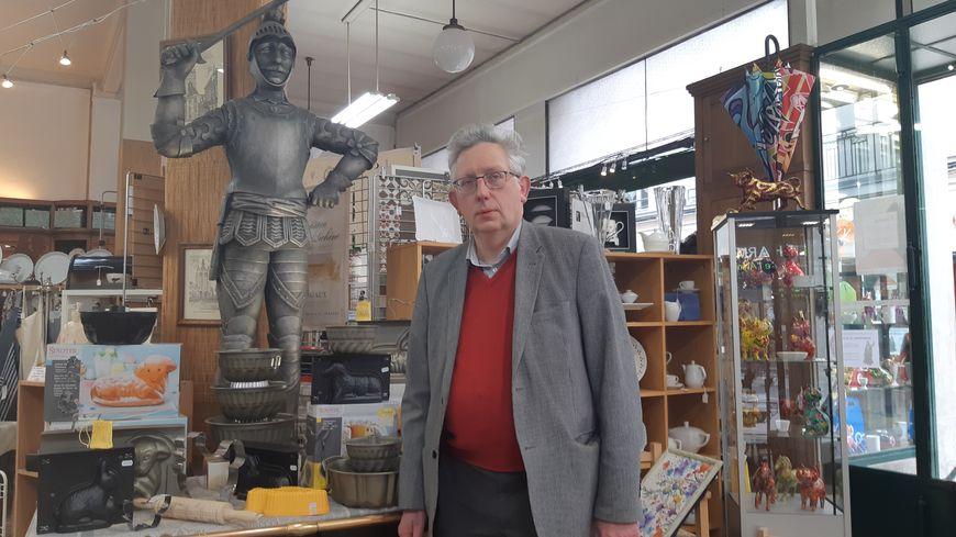 """Vincent Desfontaines, pose aux côtés de l'enseigne """"fétiche"""" de son magasin"""
