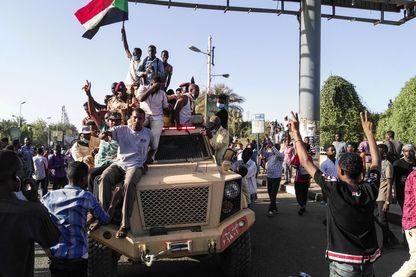 Manifestants sur un véhicule militaire, devant le quartier général des forces armées à Khartoum dimanche 7 avril, réclamant la démission du président Omar al-Bachir.