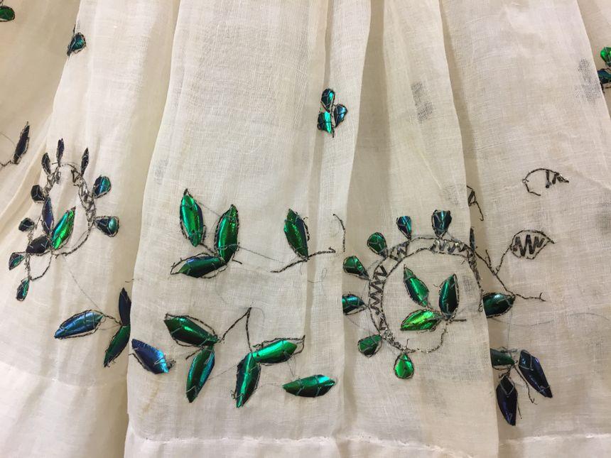 Une robe de mousseline richement parée d'ailes de scrarabées.
