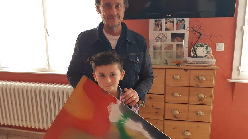 Arthur avec une de ses toiles et le réalisateur Gilles de Maistre