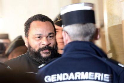 L'humoriste français Dieudonné (à gauche) fait face à un gendarme français alors qu'il arrive au palais de justice de Paris le 28 janvier 2015 pour y être jugé.