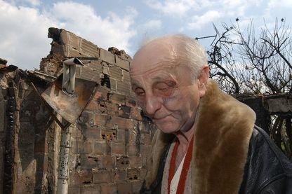"""Paul Voise, un Orléanais de 72 ans, pose le 20 avril 2002, devant sa maison du quartier de """"L'Argonne"""" incendiée la veille. Deux jeunes hommes auxquels il avait refusé de donner de l'argent l'ont roué de coups avant de brûler son pavillon"""