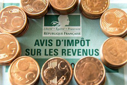 Une photo prise le 15 avril 2016 à Lille montre des pièces de cinq centimes d'euro disposées autour d'un formulaire d'évaluation fiscale français.