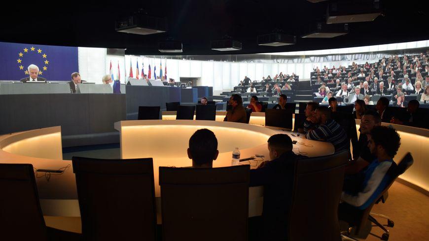 """Les visiteurs """"détenus"""" installés dans l'hémicycle reconstitué au cœur de la salle de projection à 360° du parlement de Strasbourg"""
