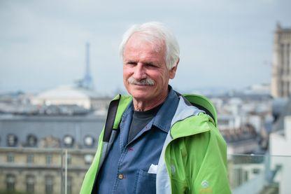 Le photographe Yann Artrhus Bertrand sur les toits de Paris, face à la Tour Eiffel