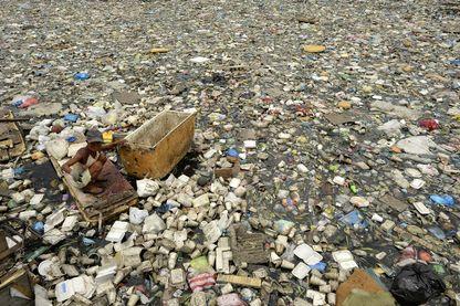 PHILIPPINES : Teresita Gapayao, 51 ans, charognarde depuis 12 ans, se promène dans les ordures à l'aide d'un radeau de fortune en polystyrène sur l'Estero de Vitas à Tondo, Manille.