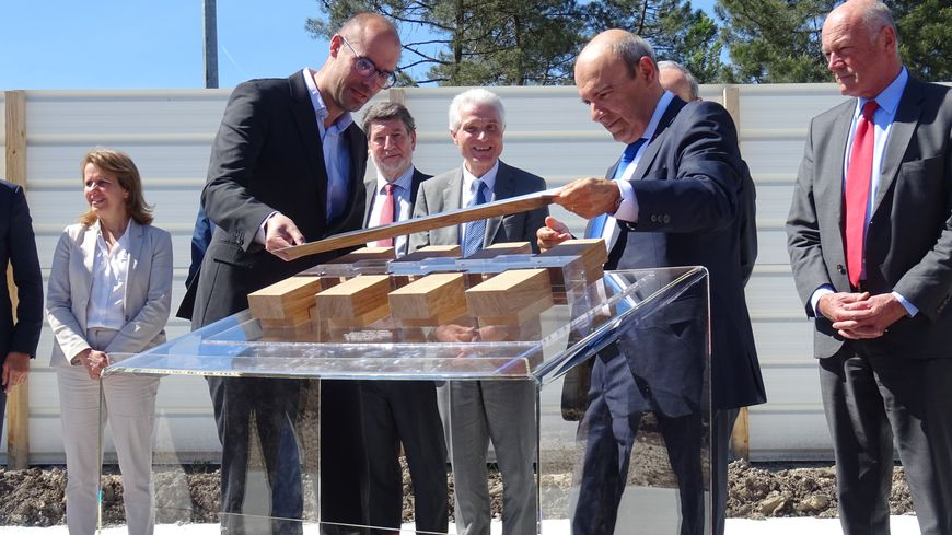 Le PDG du groupe Eric Trappier (à droite) pose symboliquement le toit de ce nouveau bâtiment sur la maquette qui le représente.