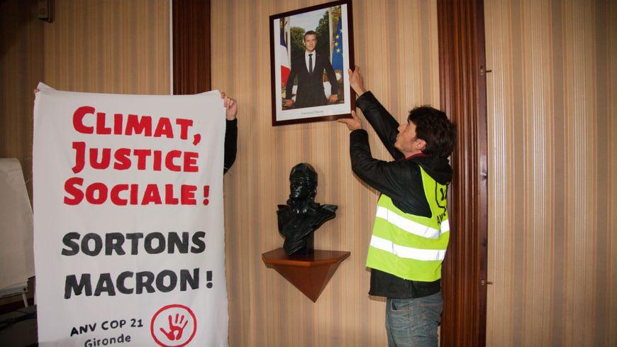 Les militants décrochent le portrait du président de la République pour contester son manque d'action face à l'urgence climatique.