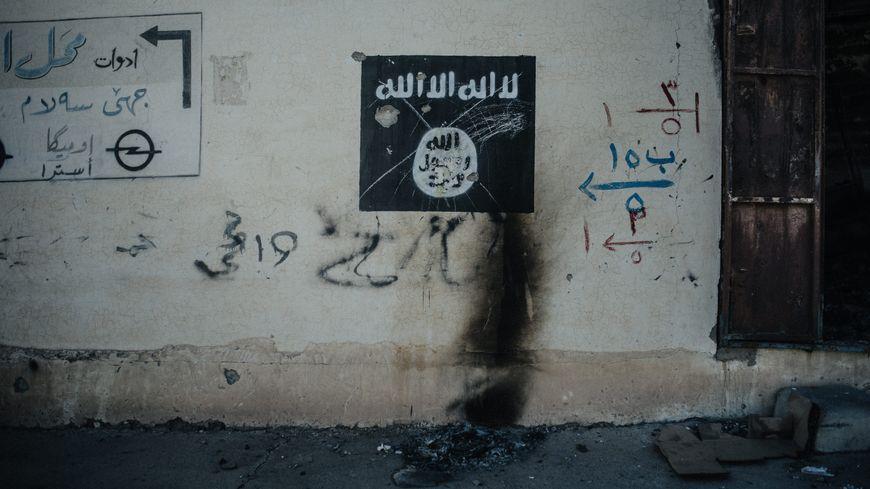 Représentation d'un drapeau de Daesh sur le mur.