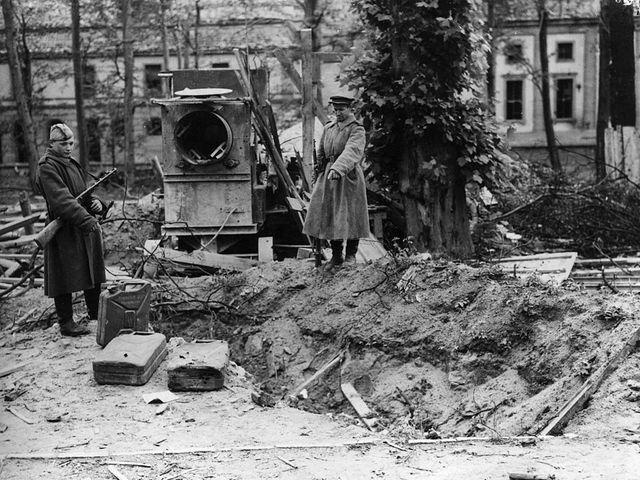 Des soldats russes sur ce qu'on dit être la tombe d'Adolf Hitler. On voit des jerricanes d'essence autour.
