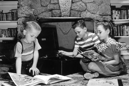 Enfants lisant dans un salon en 1955