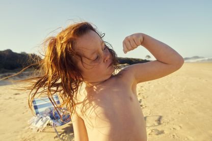 A little boy flexing his muscles at the beach