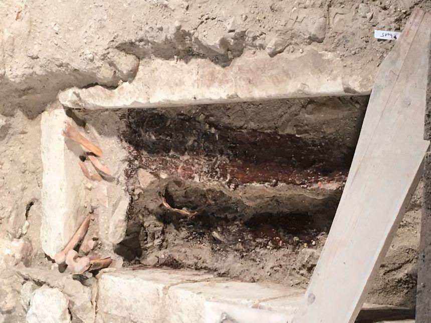 L'une des fosses a révélé une tombe du XIV siècle avec des traces de bois du cercueil et des ossements d'une précédente inhumation