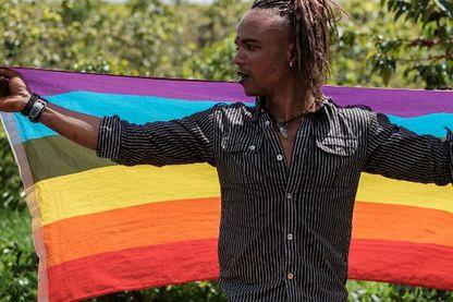 Un réfugié LGBT originaire de la République démocratique du Congo porte un drapeau arc-en-ciel lors de leur manifestation pour exiger leur protection auprès du bureau du Haut-Commissariat des Nations Unies pour les réfugiés (HCR) à Nairobi, au Kenya.