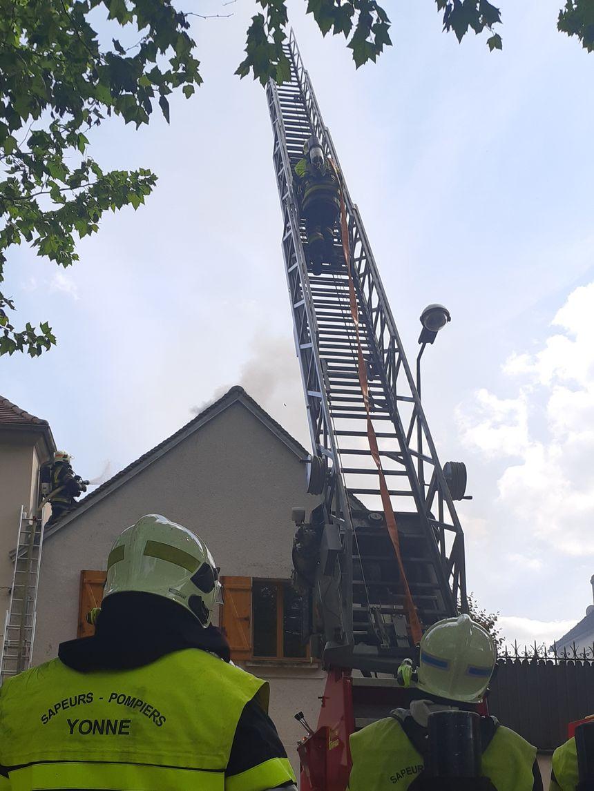 La grande échelle des pompiers de Sens en action pour éteindre le feu sous la toiture
