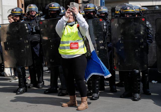 """Une manifestante """"gilet jaune"""" prend un """"selfie"""" avec les forces de l'ordre, déployées en masse pour encadrer le cortège parisien"""