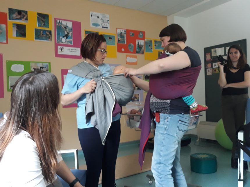 Mathilde, qui s'entraîne à l'atelier portage de bébé, pour faire la même chose, seule, avec sa petite Capucine née il y a quelques jours.
