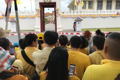 L'un des portails du Palais Royal ouvert pendant la cérémonie. Des Thaïlandais attendent, espérant apercevoir Rama X