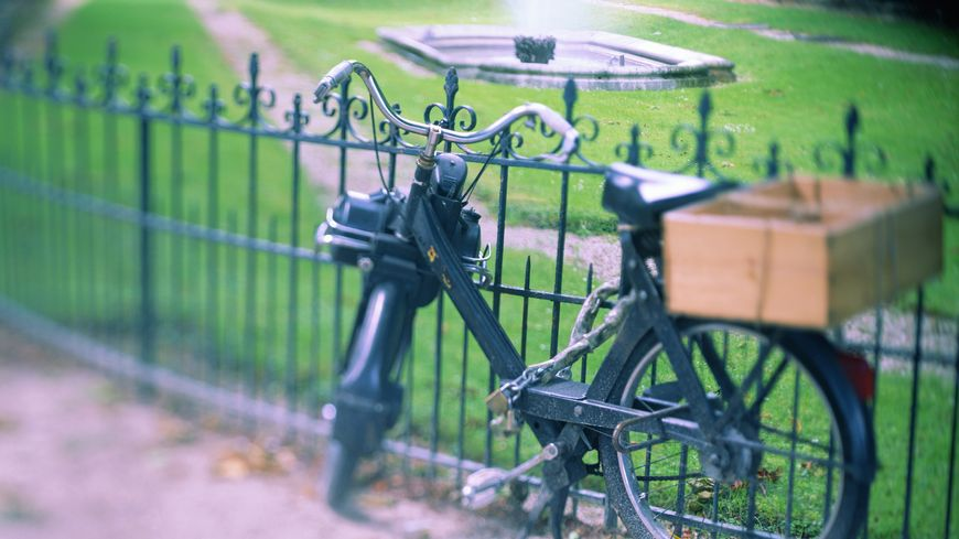 Illustration : cyclomoteur. France, Paris, bicycle chained to park fence (selective focus)