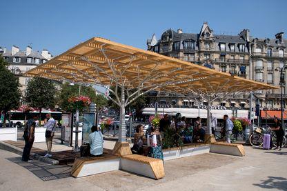 Des voyageurs profitent d'une ombrière installée devant la Gare de Lyon, à Paris