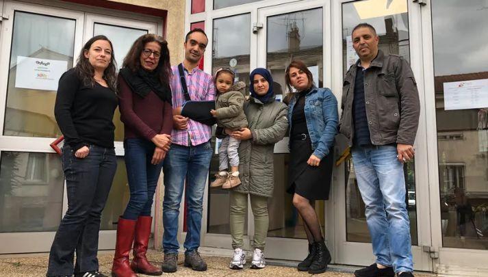 Yacine, le bras en écharpe, avec sa famille, son ami Sofiane et les membres du centre social La Rivière de Saint-Etienne