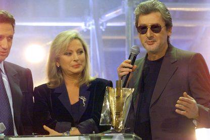 Alain Bashung, triple vainqueur des victoires de la musique sous le regard de l'animateur Michel Drucker et de la chanteuse Véronique Sanson le 20 février 1999 à l'Olympia