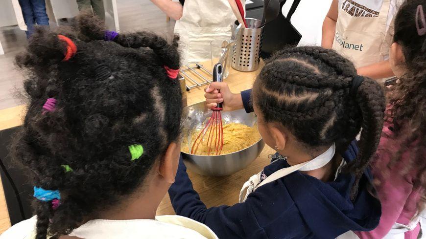 Les enfants se préparent à intégrer à leur pâte les fanes et la peau de leurs carottes