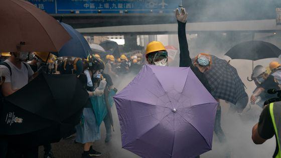 A protester throw a teargas canister to the police as another protester holds an umbrella during a demonstration on June 12, 2019 in Hong Kong