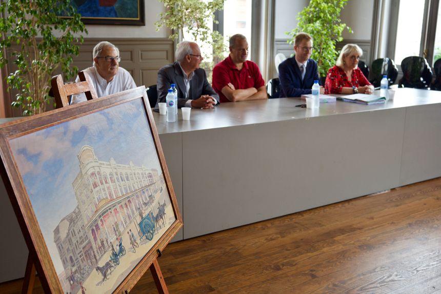 Signature de l'acte authentique d'acquisition des Nouvelles Galeries, avec au 1er plan une toile d'Henri Tayan, peintre montois, représentant le bâtiment au début des années 20