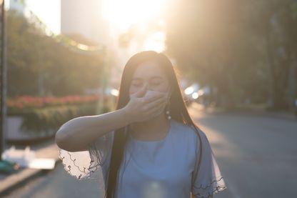 Une femme porte un masque et ajoute sa main pour se protéger de la pollution de l'air