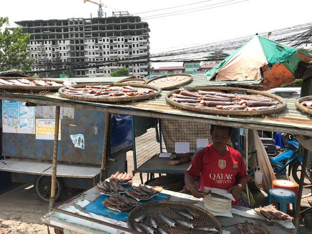 Un vendeur de poisson séché au marché de Rong Kluea. Derrière, l'immeuble en construction se trouve à Poïpet, au Cambodge. A cet endroit, la bordure du marché constitue la frontière.