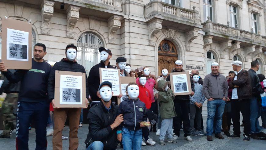 Des personnes avec un masque blanc pour les 40 adultes et enfants sans-papiers qui doivent quitter la France